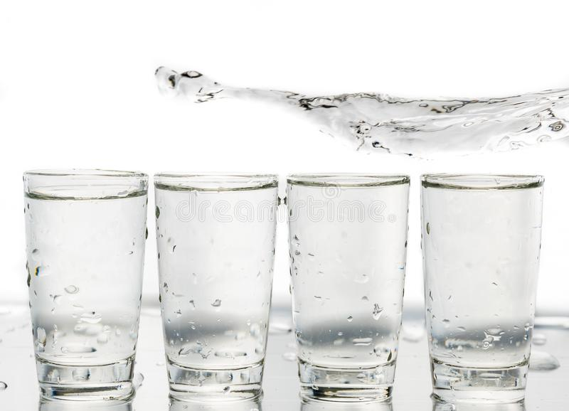 Four shot glasses close up with a splash of water in them and flying water over them.  stock images