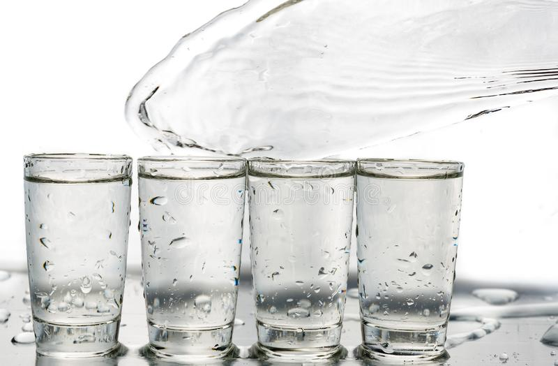 Four shot glasses close up with a splash of water in them and flying water over them.  stock image