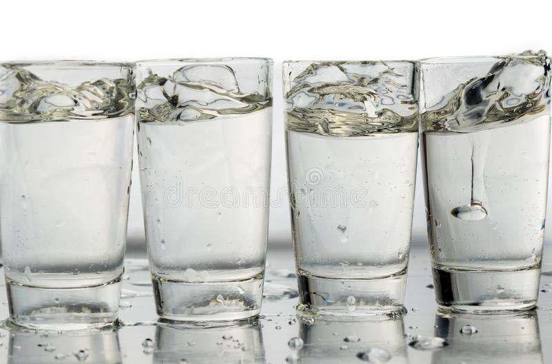 Four shot glasses close up with a splash of water in them and flying water over them.  stock photos