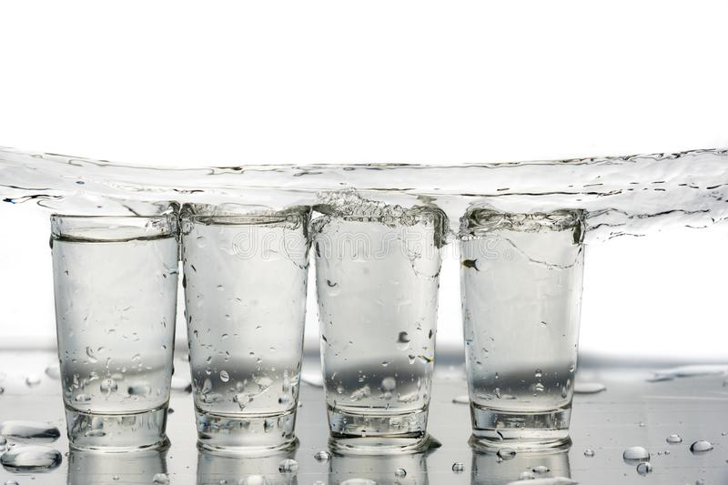 Four shot glasses close up with a splash of water in them and flying water over them.  royalty free stock photo