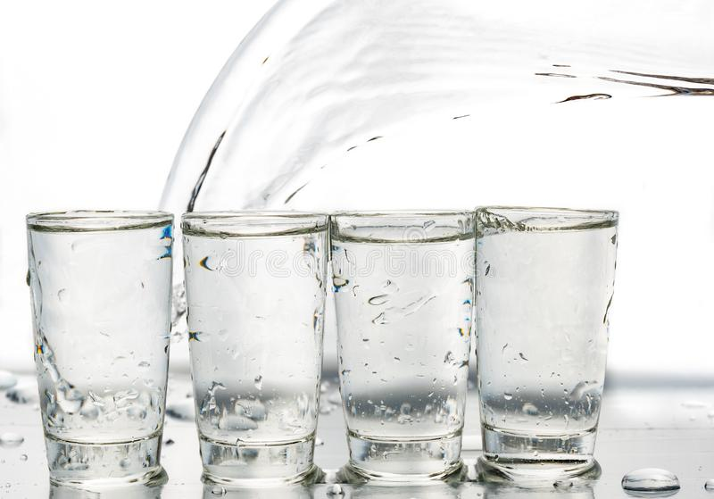Four shot glasses close up with a splash of water in them and flying water over them.  royalty free stock photography