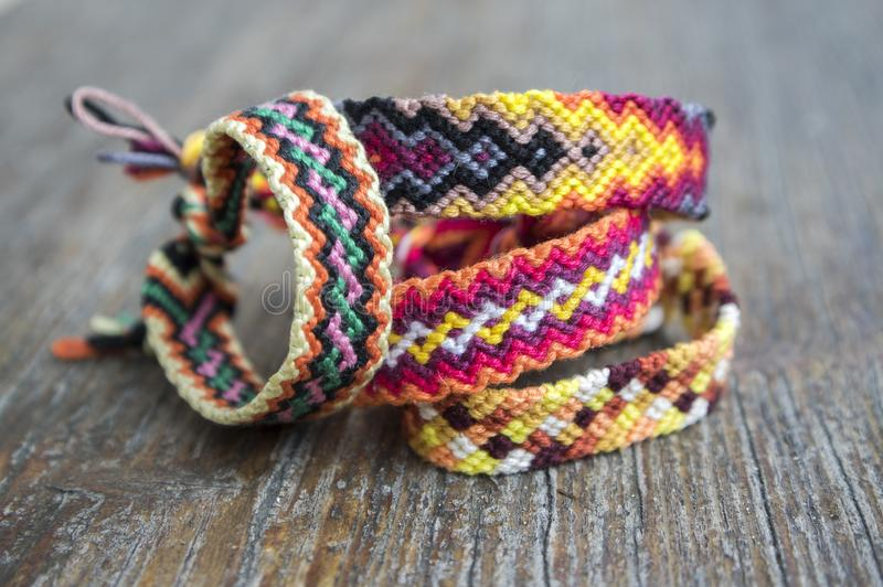 Four simple handmade homemade natural woven bracelets of friendship on wooden background, rainbow colors. Checkered pattern royalty free stock images