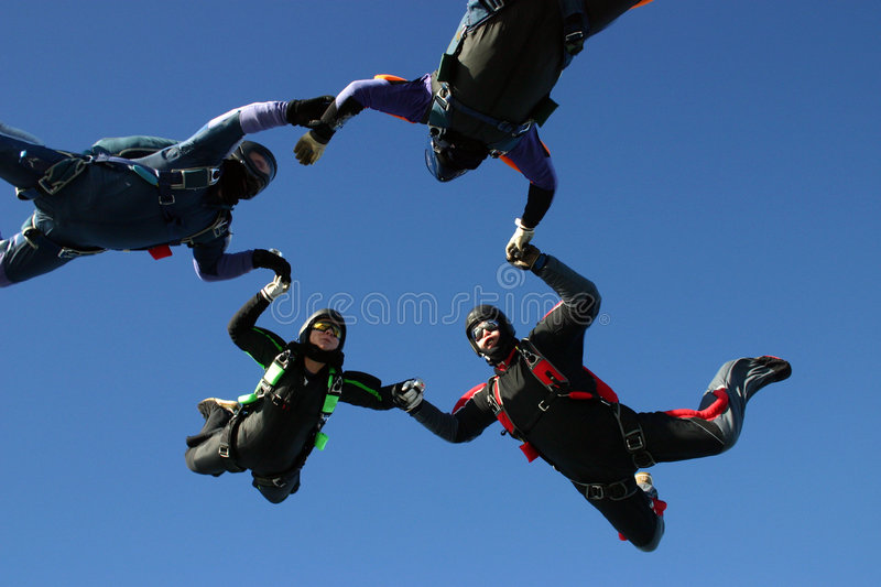 Four skydiver form a circle royalty free stock image