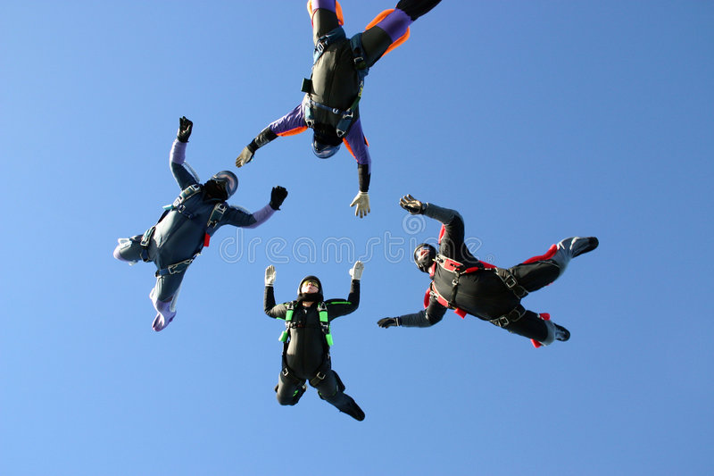 Four Skydivers building a star formation stock photos