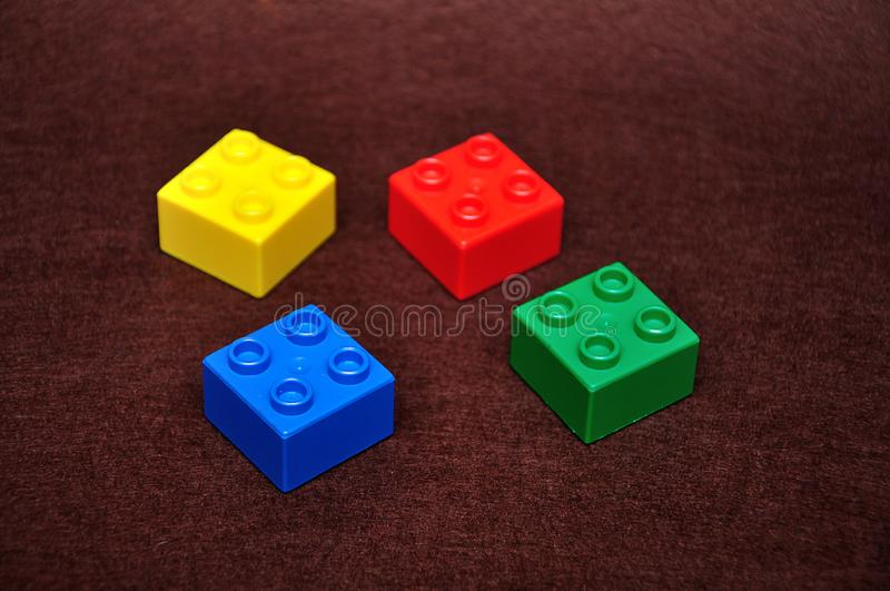 Four small building blocks of different colors. On a brown background stock images