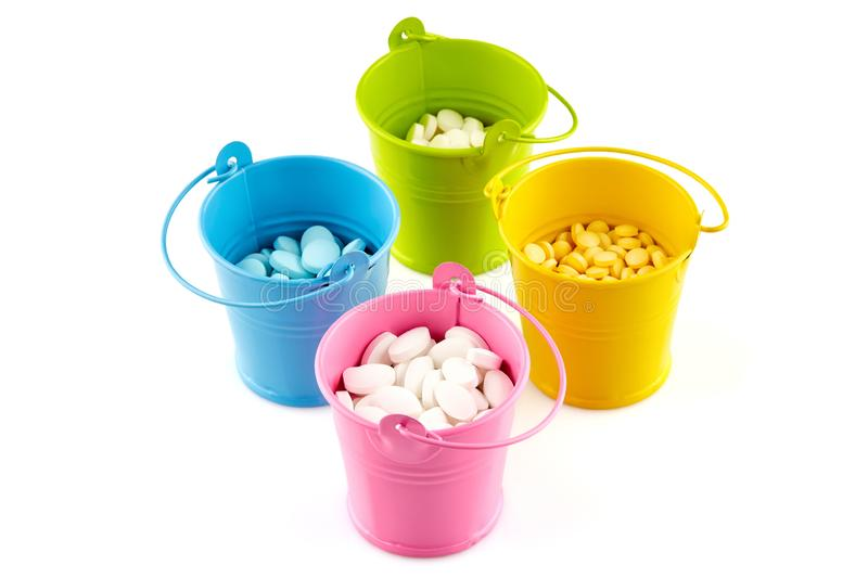 Four small colorful buckets with pills. Isolated on white background.  royalty free stock photo