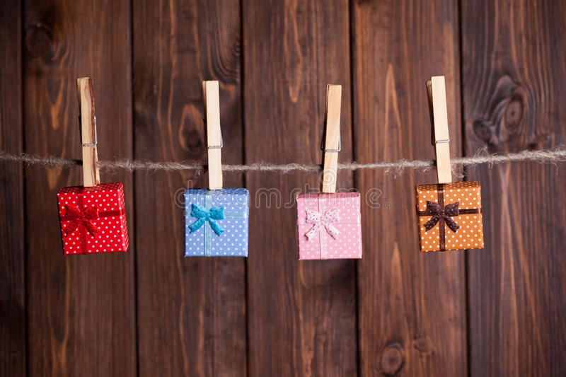 Four small gift boxes. Hanging on clothesline against wooden background royalty free stock images