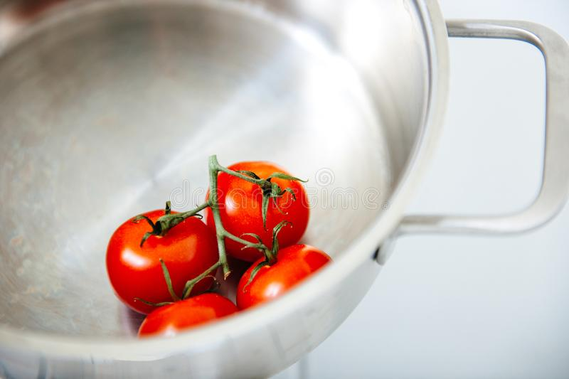 Four small tomatoes in stainless steel bowl stock photos