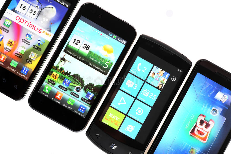 Four smart-phones. Bucharest, Romania - October 29, 2012: Four smartphones displayed in line, isolated on white, using various operating systems, like Windows stock photo