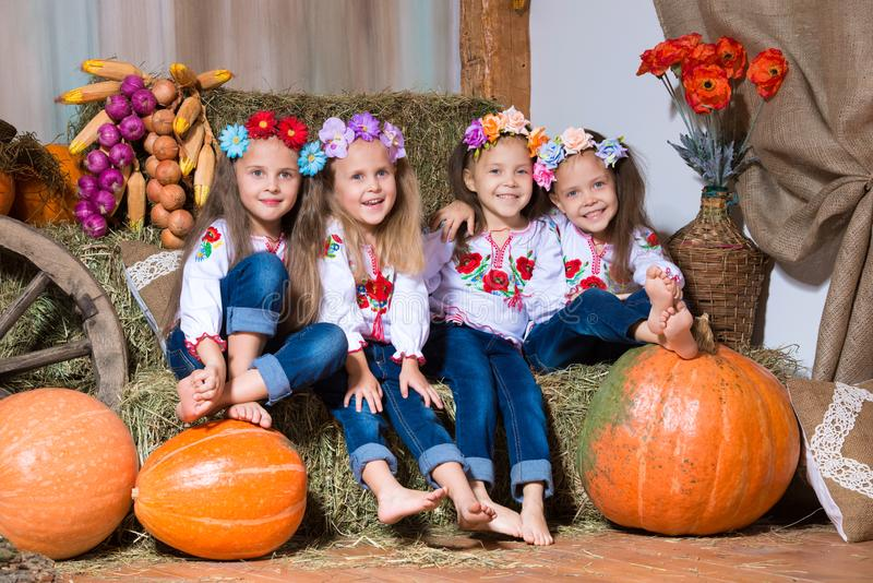 Four smiling girls twin sisters in Ukrainian wreaths sitting on haystacks. Autumn decor, harvest with pumpkins stock photos