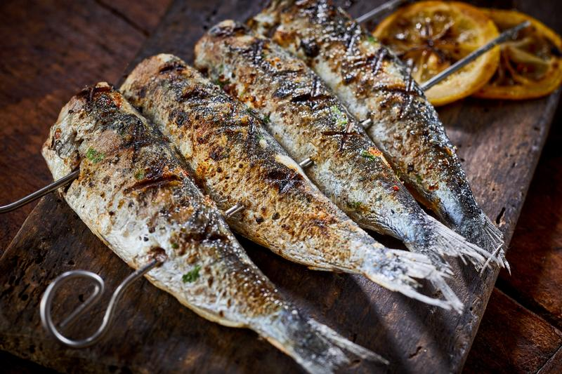 Four spicy grilled fresh fish on skewers royalty free stock photos