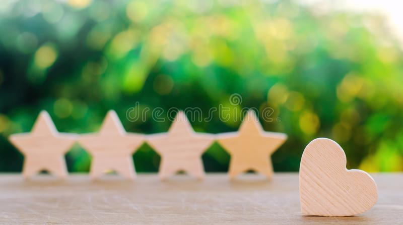 Four stars and heart on a green bokeh background. rating five stars, the choice of the editorial office and the buyer. concept of stock photos