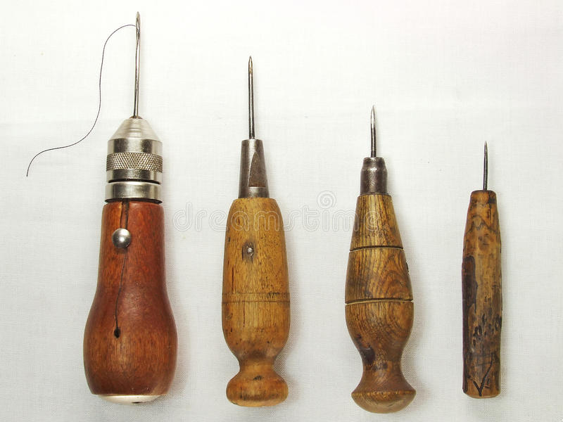 FOUR STITCHING AWLS. Four vintage stitching awls isolated on white background royalty free stock photo