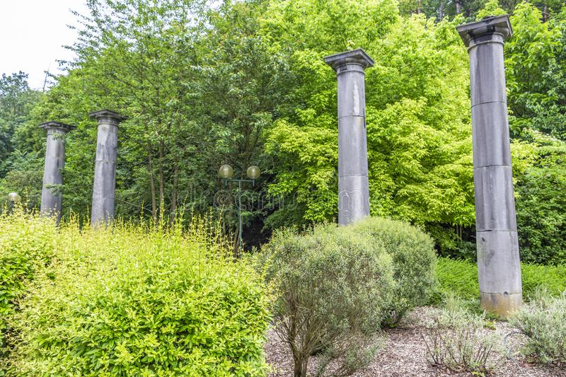 Four stone columns, the last remains of the old Pouhon Pierre le Grand or the Spring of Peter the Great in Spa, Belgium. Four stone columns in Seven o `clock royalty free stock photo