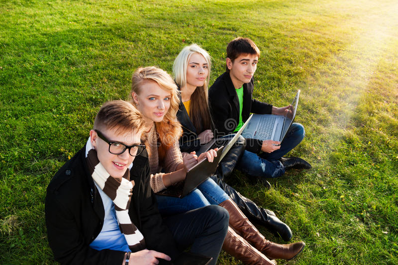 Four students with laptop. Four students sitting with laptops in the park on the grass stock photo