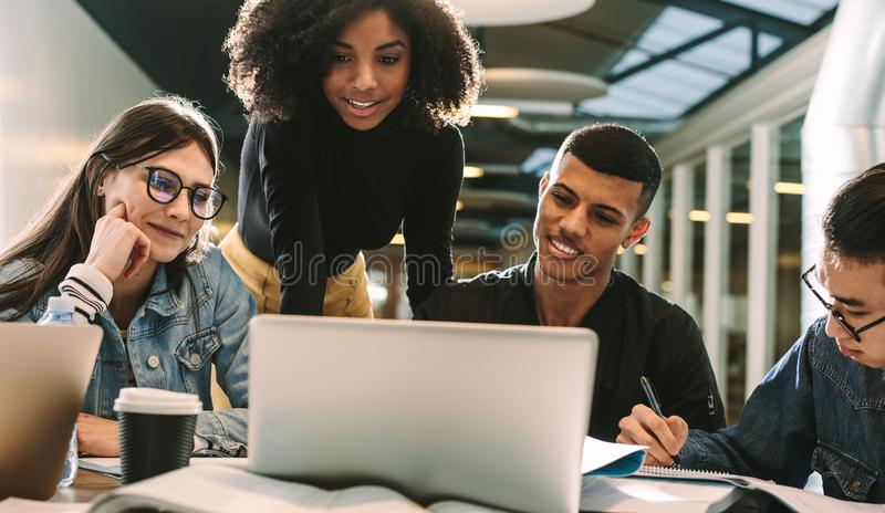 Four students using laptop for research at library stock photos