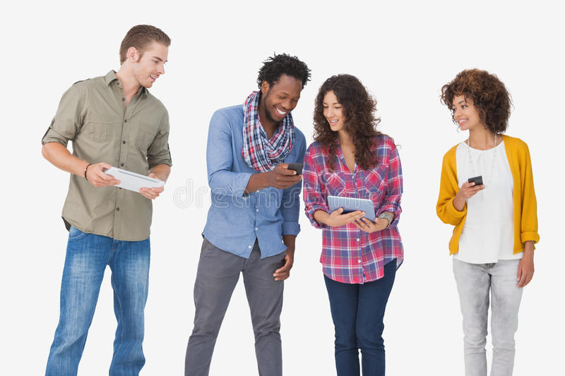 Four stylish friends looking at tablet and holding phones royalty free stock images