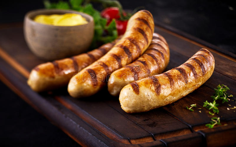 Four tasty grilled pork sausages from a BBQ royalty free stock images