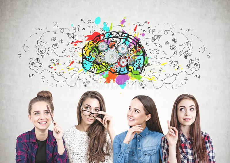 Four teen girls thinking together, cog brain. Four teen girls in casual and formal clothes are standing together and brainstorming. A concrete wall with a cog royalty free stock photography