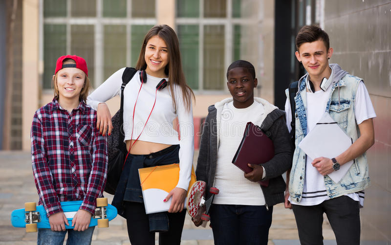 Four teenagers with folders and backpacks royalty free stock image