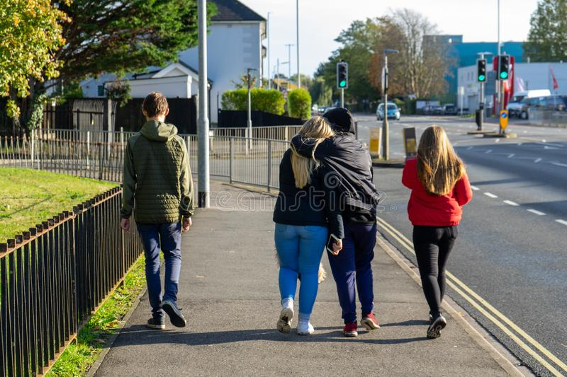 Four teenagers walking down a street with two of them hugging royalty free stock photos