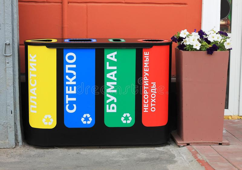 Four trash cans for separate collection of garbage with the inscription in Russian, glass, paper, plastic, unsorted waste. royalty free stock photos