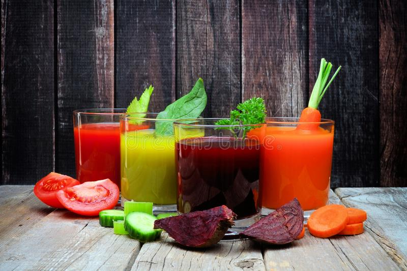 Four types of healthy vegetable juice with a dark wood background. Four glasses of healthy vegetable juice with scattered vegetables and a dark wood background royalty free stock photo