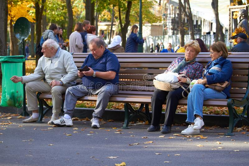 Four unidentified happy retired people rest on a bench, autumn scene royalty free stock images