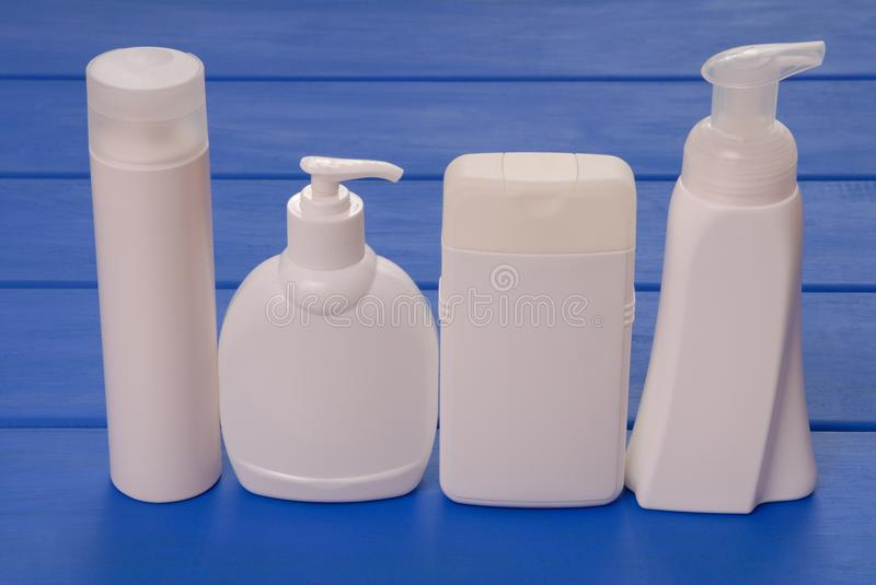 four vials of cosmetics, cosmetic bottles, assortment of cosmetic flasks, health and beauty royalty free stock images