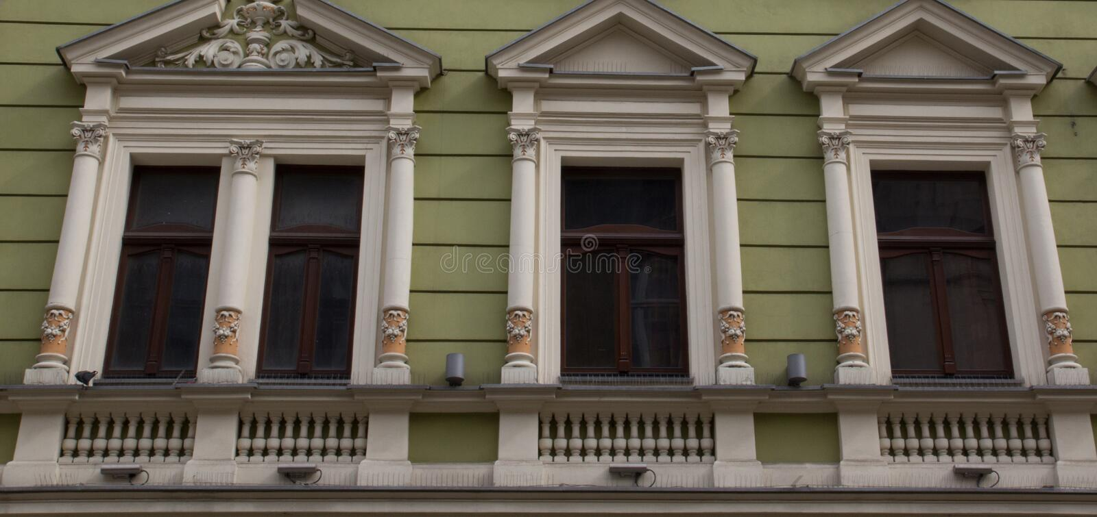 Four vintage design windows on the facade of the old house.  royalty free stock images