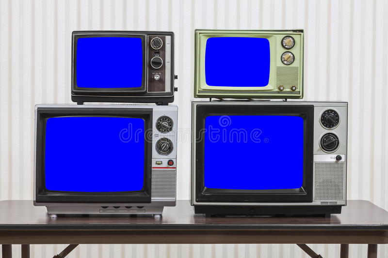 Four Vintage Televisions With Chroma Key Blue Screens. Four vintage televisions on table with chroma key blue screens royalty free stock image