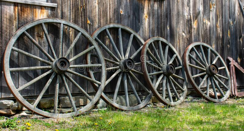 Four Wagon Wheels lay against an old barn at Williams Barn stock images
