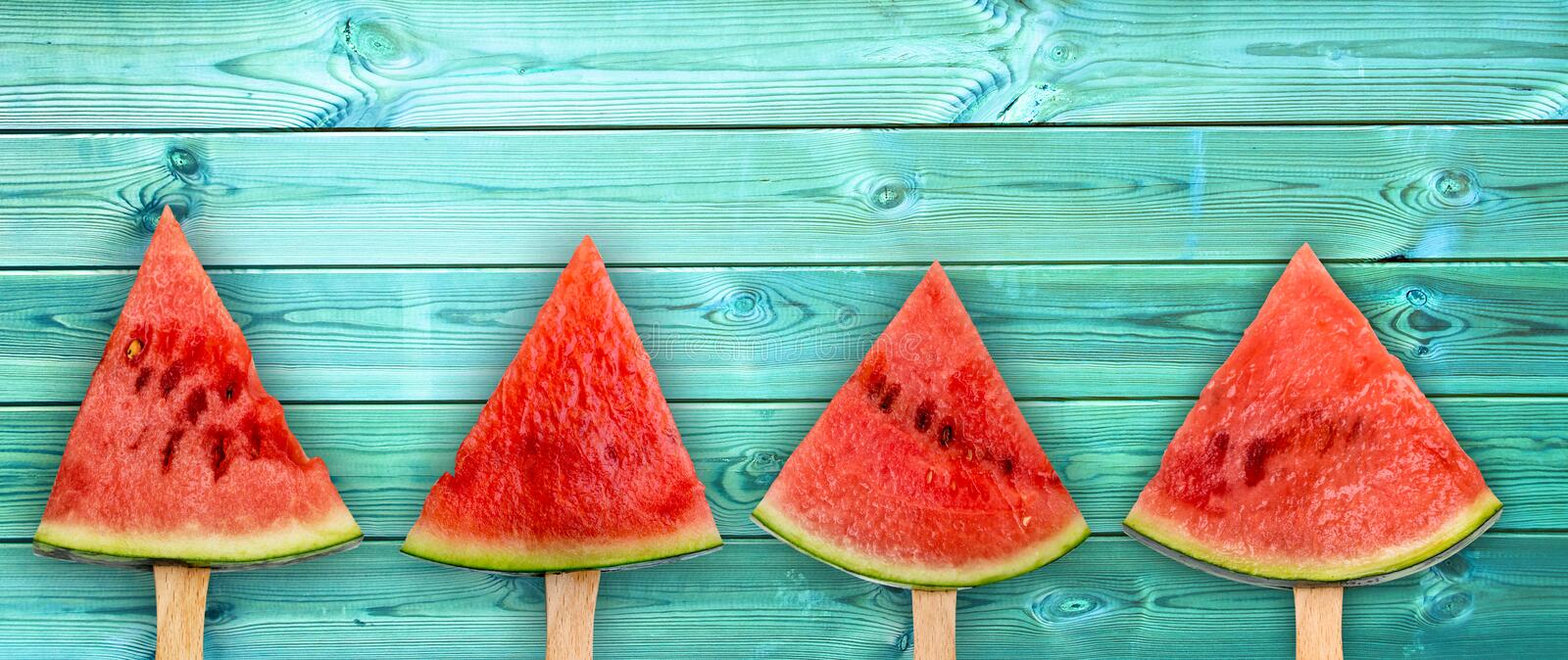Four watermelon slice popsicles on panoramic blue wood background, fresh fruit concept royalty free stock images