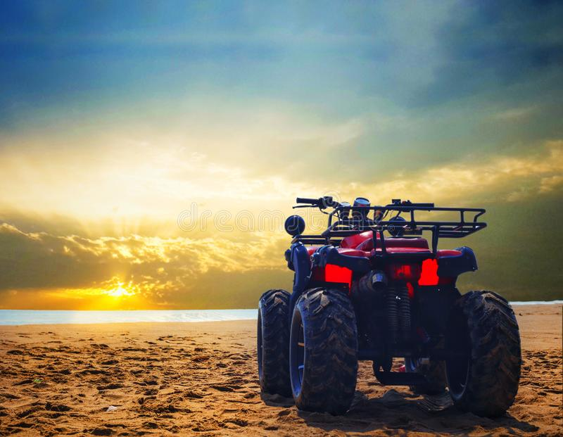 Four wheeler dirt bike on sand of sea beach during sunrise with dramatic colourful sky stock images