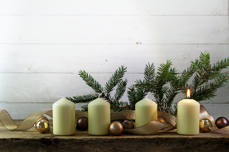 Four white candles, one of them burning on the first advent christmas decoration with spruce twigs, baubles and a golden ribbon o stock photos
