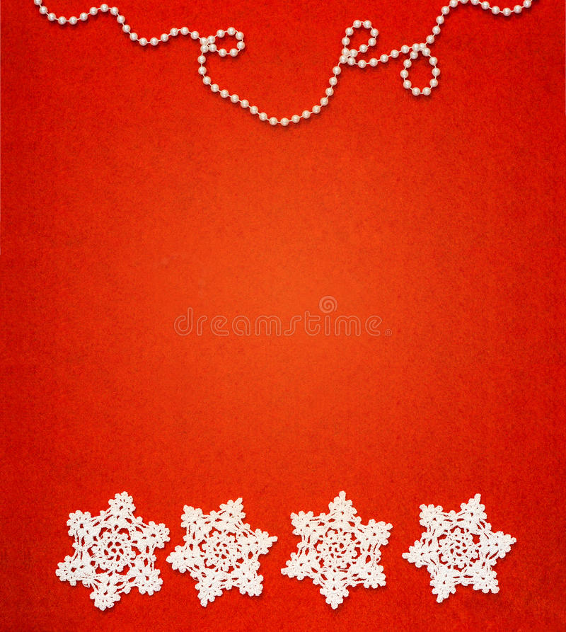 Four white crochet snowflakes in a row with a chain of white bead spheres on the top royalty free stock photography