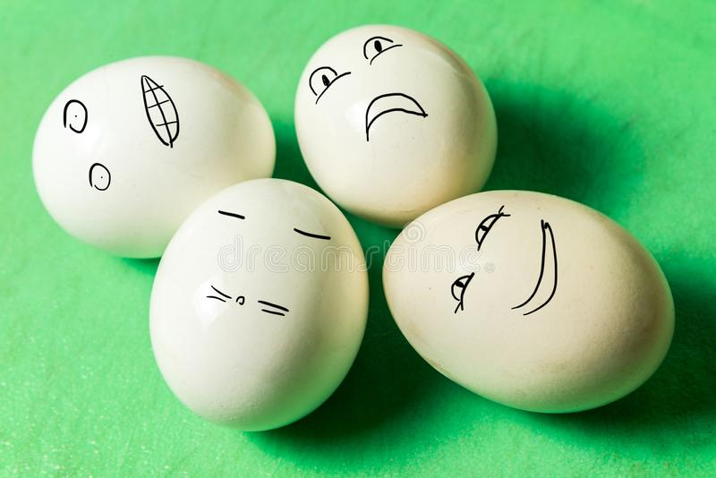 Four white eggs with different face grimaces on green board. Horizontal frame royalty free stock photos