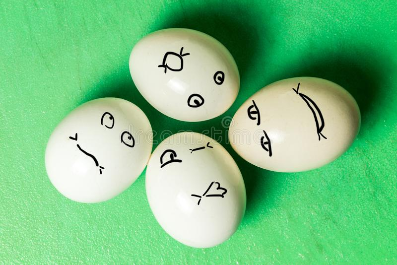 Four white eggs with different face grimaces on green board. Horizontal frame stock photos