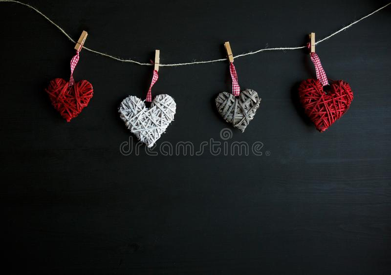 Four white and red hearts on black wooden table. Valentines, spring background. Mock up with copyspace. happy mothers day royalty free stock photos