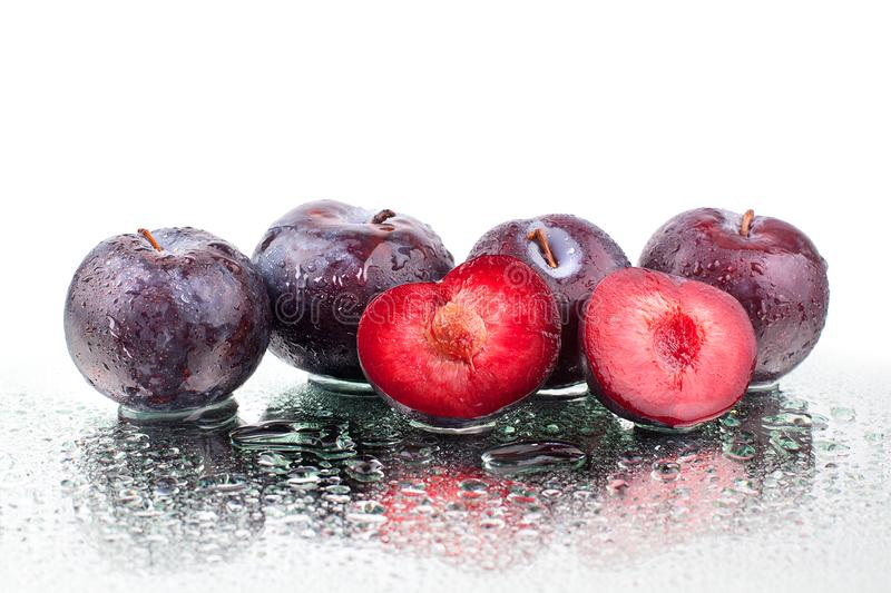 Four purple ripe plums and one cutted plum on white mirror background isolated close up macro in row in water drops stock photo