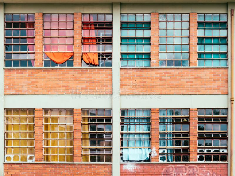 Windows with broken glass and color courtain. Four windows of a brick building with broken glass and color courtain stock images