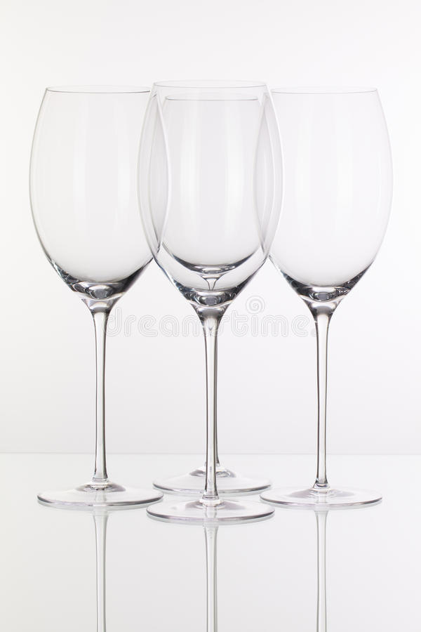 Four wine glasses on a glass desk stock photos