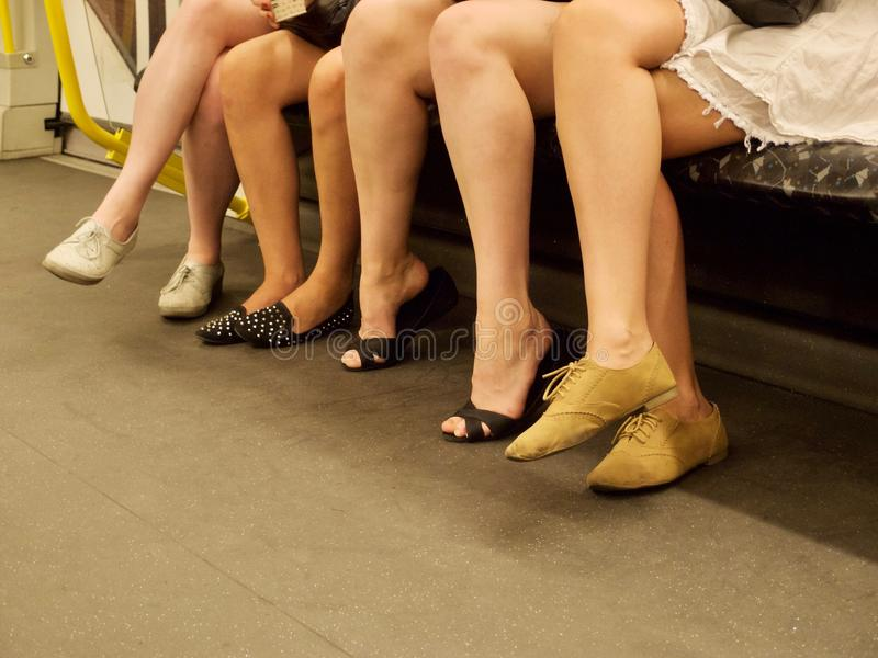 Four women with bare legs with bare legs sitting. Low section of four women with bare legs wearing casual summer shoes while sitting down in the public royalty free stock image