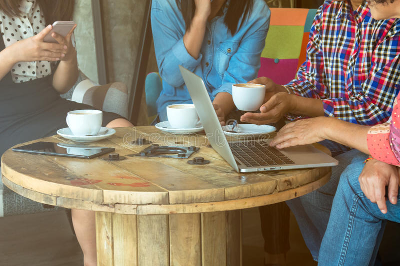 Four women do meeting by sharing information from notebook and drinking coffee in coffee shop. With warm light flare tone royalty free stock photography