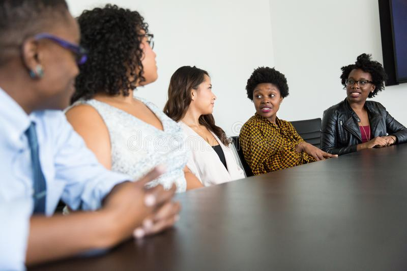 Four Women and One Man Sitting Near Table Inside Room stock images