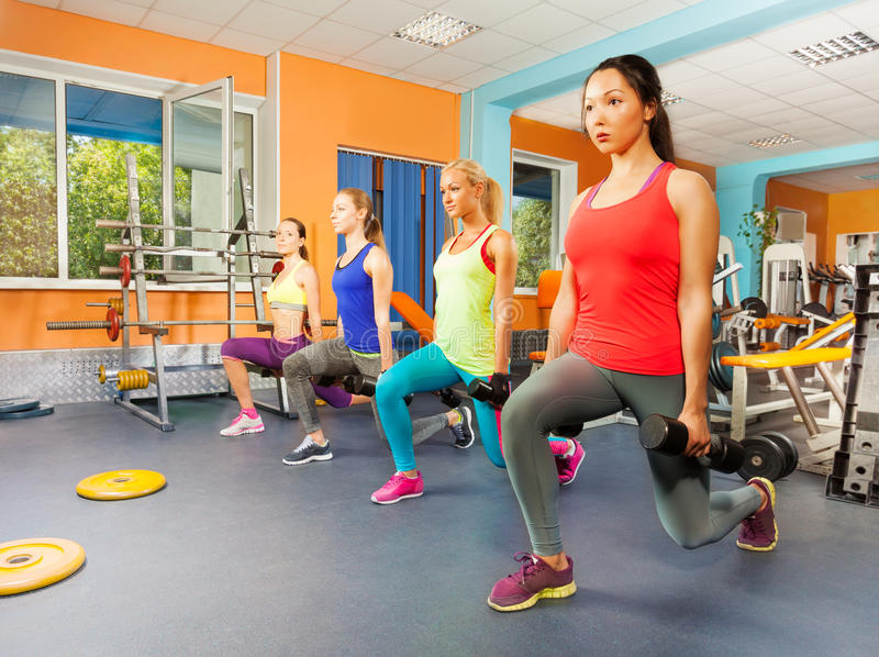 Four women in a row excursing inside fitness club royalty free stock image