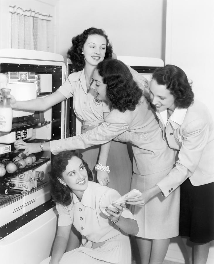 Four women taking things from a refrigerator royalty free stock photos