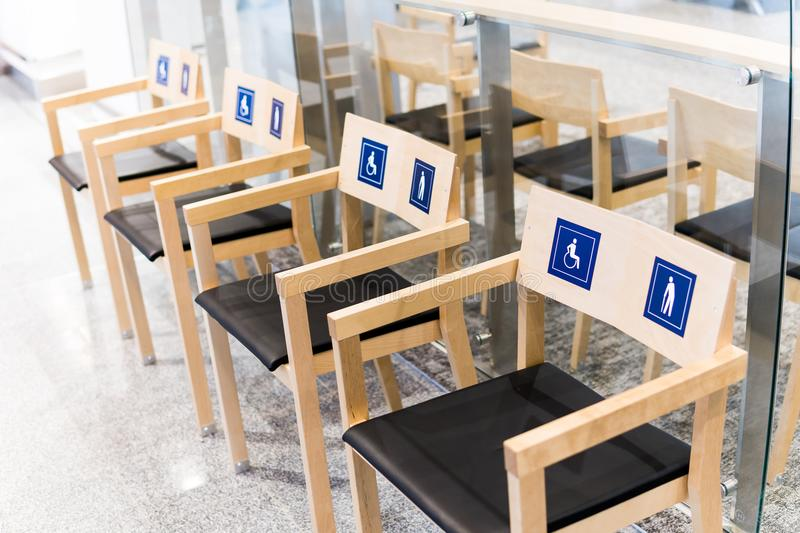 Four wooden chairs at the airport with signs for the disabled and the elderly. Allocation of public seats to the royalty free stock photo