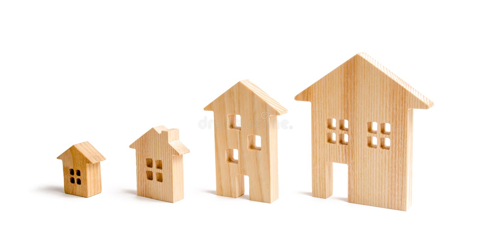 Four wooden houses stand in ascending order on a white background. Isolate The concept of increasing population density. And high-rise buildings. Agglomeration stock photos