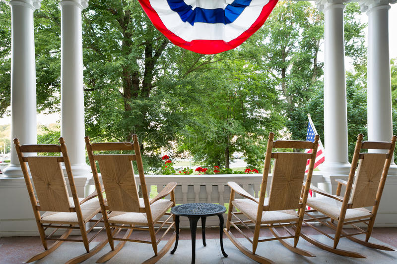 Four wooden rocking chairs and the American flag. Four vacant wooden rocking chairs lined up on a patio overlooking a lush garden below a draped American flag stock image